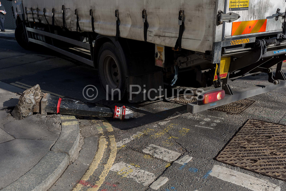 As a potential public liability insurance claim, an obstacle in the road surface where a damaged bollard lies horizontal, knocked over by a vehicle on 13th February 2017, in the City of London, United Kingdom.