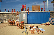 Stopping work for a moment to pose for a portrait on the sea wall at Lowestoft, Suffolk, England, a team of the resort's lifeguards show their youth, fitness and bodies beautiful, displaying themselves in the sun of a fine summer day. There is only one female member but some are standing on the wall while others are seated in deck chairs, a ladder seat or on the hot sand near three sexy girls are are sunning themselves near a railing. Wearing bikinis one is not asleep but eyeing-up some of the alpha-male specimens  on show wearing only red shorts. Meanwhile, holidaymakers walk past with ice-creams. It is a bright scene and obviously a busy time for these safety experts when tourists forever get themselves into danger in the sea and surf. Currents here make for a hazardous experience for those unable to swim out of trouble.