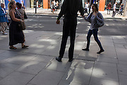 A tall leafleteer hands out marketing information to passers-by in Oxford Street, London.