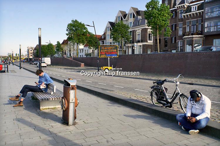 Nederland, Nijmegen, 26-4-2020 Een elektronisch mededelingenbord van de gemeente herinnert de mensen eraan voldoende afstand te houden, en dat het verboden is een samenscholing te hebben op de waalkade . Groep,groepen,samenscholing,verbod,verboden,samenscholingsverbod Foto: Flip Franssen