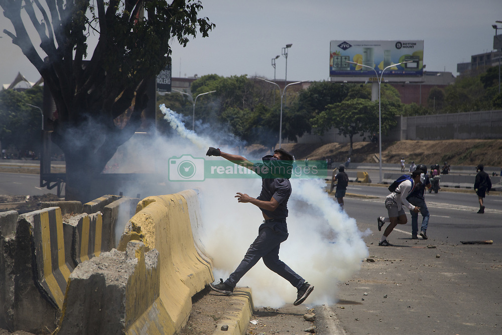 May 1, 2019 - Caracas, Venezuela - An anti-government protester throws Molotov cocktails during clashes with security forces in the surroundings of La Carlota military base in Caracas during the commemoration of May Day after a day of violent clashes on the streets of the capital spurred by Venezuela's opposition leader Juan Guaido's call on the military to rise up against President Nicolas Maduro. (Credit Image: © Jonathan Lanza/NurPhoto via ZUMA Press)