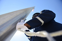 A U.S. Air Force Base Honor Guard member from Tyndall Air Force Base, Fla., lowers the installation flag prior to hoisting the POW/MIA flag during the retreat ceremony for Tyndall's 30th Annual POW/MIA 24-hour Vigil Run at Flag Park Oct. 4, 2018. National POW/MIA Recognition Day is traditionally observed on the third Friday in September each year. (U.S. Air Force photo by Airman 1st Class Solomon Cook)
