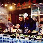 Street vendors prepare food at their stall in Tianshui, Gansu province, China