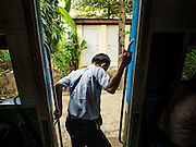26 OCTOBER 2015 - YANGON, MYANMAR: A conductor hops off the Yangon Circular Train as it pulls into a station. The Yangon Circular Railway is the local commuter rail network that serves the Yangon metropolitan area. Operated by Myanmar Railways, the 45.9-kilometre (28.5mi) 39-station loop system connects satellite towns and suburban areas to the city. The railway has about 200 coaches, runs 20 times daily and sells 100,000 to 150,000 tickets daily. The loop, which takes about three hours to complete, is a popular for tourists to see a cross section of life in Yangon. The trains run from 3:45 am to 10:15 pm daily. The cost of a ticket for a distance of 15 miles is ten kyats (~nine US cents), and for over 15 miles is twenty kyats (~18 US cents).    PHOTO BY JACK KURTZ