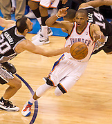 June 2, 2012; Oklahoma City, OK, USA; Oklahoma City Thunder guard Russell Westbrook (0) is fouled by San Antonio Spurs guard Manu Ginobili (20) during the second half of a playoff game at Chesapeake Energy Arena.  Mandatory Credit: Beth Hall-US PRESSWIRE