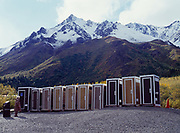 """""""Which one to choose?""""  Lone woman and the Toklat River line-up, ten outhouses in a row, Denali National Park, Alaska."""