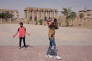 Young Egyptians pass in front of the ancient Egyptian columns of Luxor Temple with the Mosque of Abu el-Haggag's, far right, Luxor Temple, Nile Valley, Egypt. The temple behind was built by Amenhotep III, completed by Tutankhamun then added to by Rameses II. Towards the rear is a granite shrine dedicated to Alexander the Great and in another part, was a Roman encampment. The temple has been in almost continuous use as a place of worship right up to the present day.