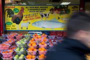Fruit seller in Whitechapel in East London. Each bowl of fruit is £1. Halal meat is also sold here.