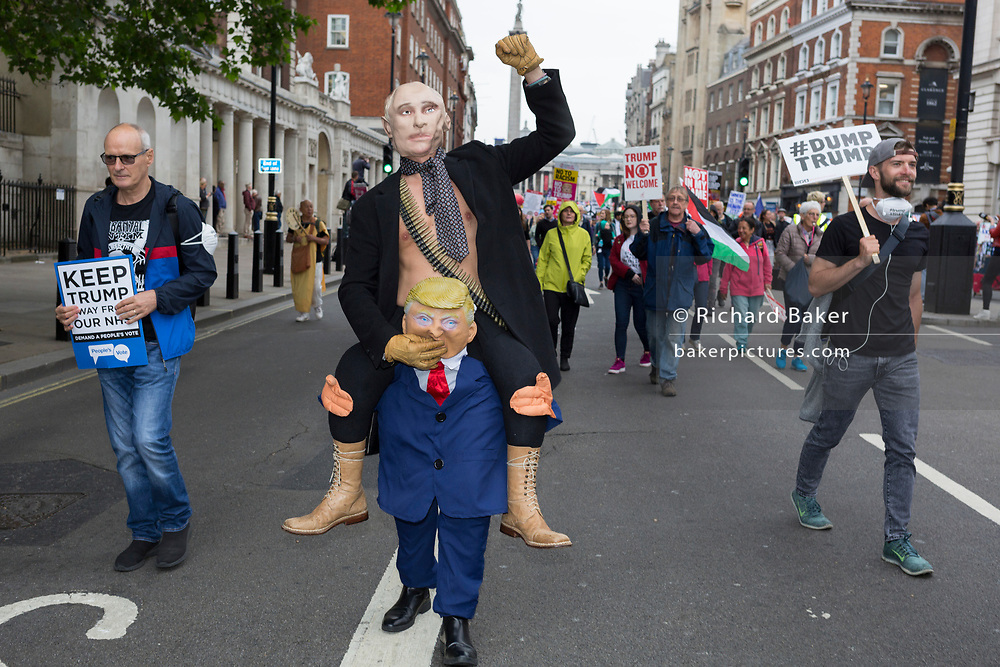 On US President Donald Trump's second day of a controversial three-day state visit to the UK, figures of Russian President Vladimir Putin being given a piggyback on Trump, march alongside protesters voicing their opposition to the 45th American President, down Whitehall, on 4th June 2019, in London England.