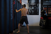 Batgerel Danaa of Mongolia works on the heavy bag with a portrait of UFC light heavyweight Jon Jones hanging on the wall behind him at Jackson Wink MMA in Albuquerque, New Mexico on June 9, 2016.