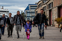 ATHENS, GREECE - FEBRUARY 04: A family of refugees walk toward the buses that will take them to the Macedonian border after disembarking a ferry at the Pireaus port from the Greek islands on February 04, 2015 in Athens, Greece. Thousands of refugees arrive every day by ferries fleet by private companies from the Greek islands to the Pireaus port. Photo: © Omar Havana. All Rights Are Reserved
