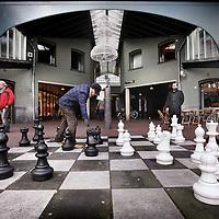 Nederland, Amsterdam , 7 december 2011..Schaken op het Max Euweplein..Playing public chess with huge chessmen on the Max Euwe sqaure in Amsterdam.