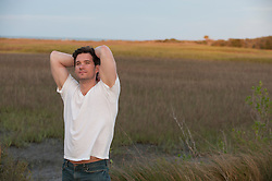 man with his arms behind his head enjoying the marshlands of Charleston, South Carolina