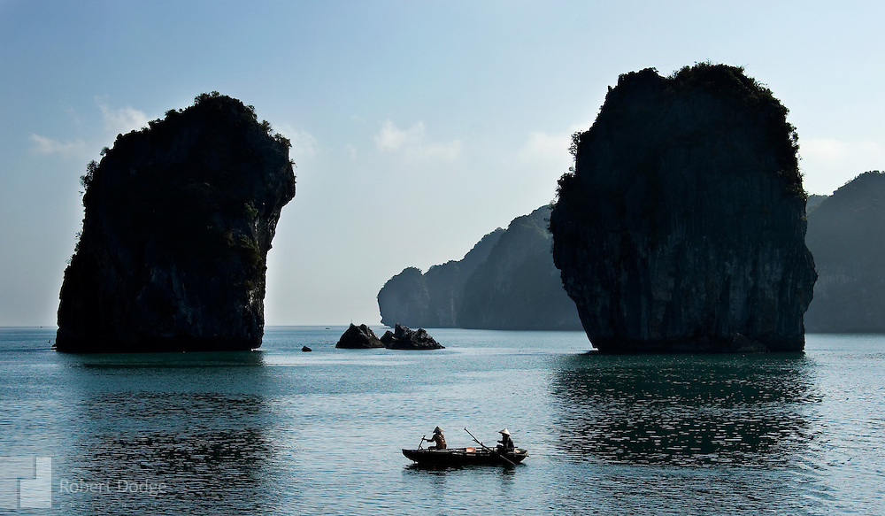 Two fishermen make their way among the limestone islands as they pursue a catch in Halong Bay. There about 3,000 of the islands in the scenic bay which is a UNESCO World Heritage Site. Robert Dodge, a Washington DC photographer and writer, has been working on his Vietnam 40 Years Later project since 2005. The project has taken him throughout Vietnam, including Hanoi, Ho Chi Minh City (Saigon), Nha Trang, Mue Nie, Phan Thiet, the Mekong, Sapa, Ninh Binh and the Perfume Pagoda. His images capture scenes and people from women in conical hats planting rice along the Red River in the north to men and women working in the floating markets on the Mekong River and its tributaries. Robert's project also captures the traditions of ancient Asia in the rural markets, Buddhist Monasteries and the celebrations around Tet, the Lunar New Year. Also to be found are images of the emerging modern Vietnam, such as young people eating and drinking and embracing the fashions and music of the West. His book. Vietnam 40 Years Later, was published March 2014 by Damiani Editore of Italy.