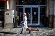 "A woman with face mask passing the famous and closed hotel ""Jalta"" at Wenceslas Square. On March 1st, 2021 the state of emergency in the Czech Republic was reinstalled because of fast increasing numbers in infections. The lockdown was reinstated and the restriction of the free movement of people has taken effect. Currently, the country remains at the highest stage of the anti-epidemiological system and the newly imposed restriction will last at least three weeks to curb the epidemic."