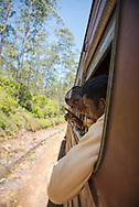 Two Sri Lankan males look out the window while traveling by train between the towns of Nuwara Eliya and Ella in Sri Lanka (April 9, 2017)