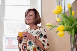 Senior woman dreaming while drinking tea in kitchen Munich, Bavaria, Germany