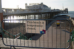 © Licensed to London News Pictures. 25/12/2014. Brighton, UK. Brighton Beach closed by barriers. The event has been cancelled by Brighton and Hove Swimming Club due to Health and Safety fears for the public. Swimmers have been warned by Brighton and Hove City Council to stay away from the sea and advised they have closed the beach to prevent people entering the sea around the Pier. Photo credit : Hugo Michiels/LNP