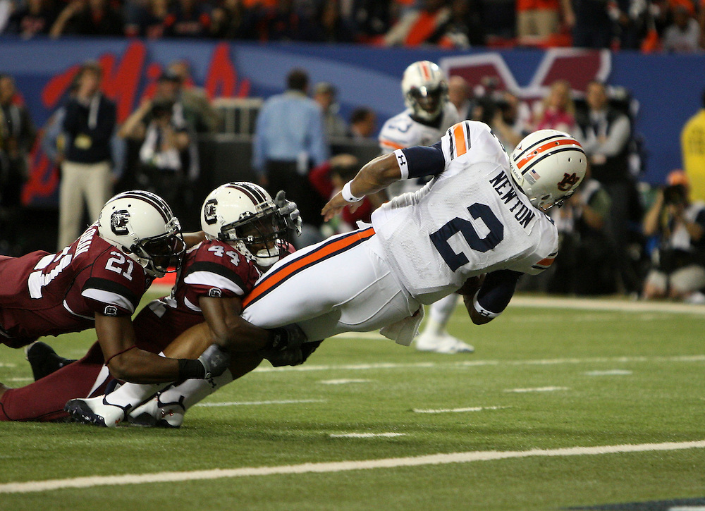 ATLANTA - DECEMBER 4:  Quarterback Cam Newton #2 of the Auburn Tigers dives in for a first quarter touchdown while safety DeVonte Holloman #21 and linebacker Tony Straughter #44 of the South Carolina Gamecocks try to stop him during the 2010 SEC Championship at Georgia Dome on December 4, 2010 in Atlanta, Georgia. (Photo by Mike Zarrilli/Getty Images)