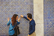 A couple near a ceramic tile-decorated facade at Madragoa district in Lisbon