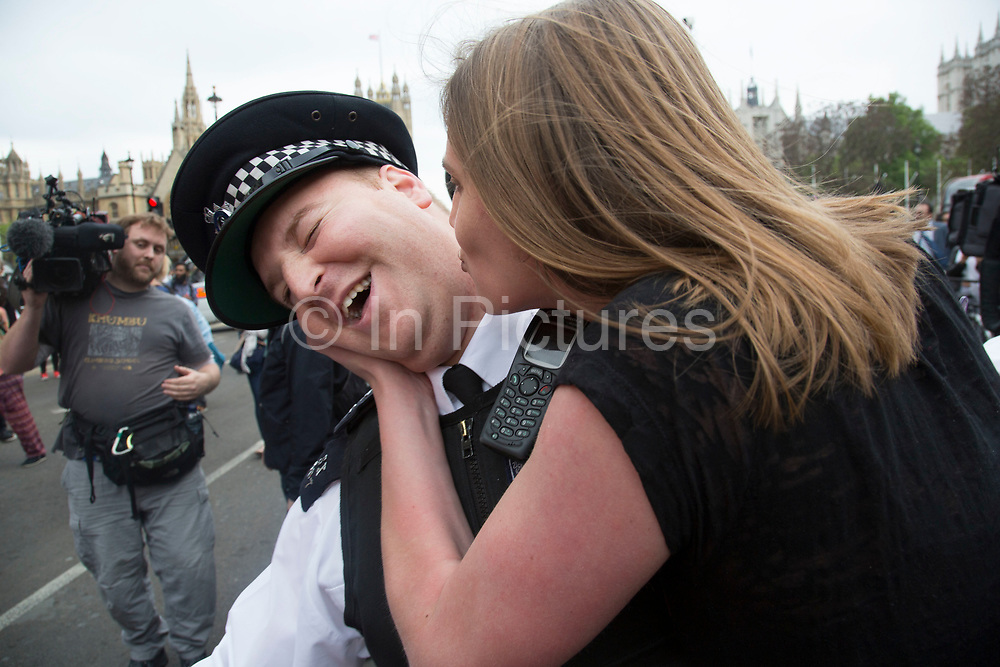 London, UK. Wednesday 27th May 2015. Young protester plays gently with police, kissing one policeman  as students demonstrate in Westminster against Tory Party cuts. The protest was focussed on a number of subjects including spending cuts but generally was a mark of displeasure and concern as to what the Conservatives will do while in power.