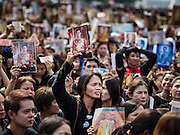 22 OCTOBER 2016 - BANGKOK, THAILAND:  Mourners hold up portraits of the late Bhumibol Adulyadej, the King of Thailand, during the singing of the King's Anthem on Sanam Luang Saturday. Sanam Luang, the Royal Ceremonial Ground, was packed Saturday with more than 100,000 people mourning the Monarch's death. The King died Oct. 13, 2016. He was 88. His death came after a period of failing health. Bhumibol Adulyadej was born in Cambridge, MA, on 5 December 1927. He was the ninth monarch of Thailand from the Chakri Dynasty and is also known as Rama IX. He became King on June 9, 1946 and served as King of Thailand for 70 years, 126 days. He was, at the time of his death, the world's longest-serving head of state and the longest-reigning monarch in Thai history.      PHOTO BY JACK KURTZ
