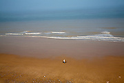 Overhead oblique view of a man walking across wide sandy beach at low tide, Overstrand, Norfolk, England