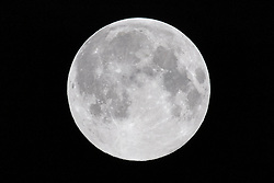 © Licensed to London News Pictures. 27/04/2021. London, UK. The first Pink Supermoon appears its brightest at 04.21am. A Supermoon occurs when the full Moon at the same time the Moon is at (or close to) perigee. This makes it appear up to 14 per cent bigger and 30 per cent brighter than a full Moon at apogee. Photo credit: Ray Tang/LNP