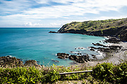 Views from the North Coast of a secluded pebbly and rocky cove and the reen cliffs and headland in Jersey, CI