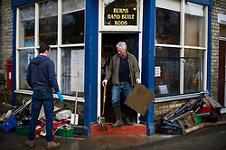© Licensed to London News Pictures. 29/12/2015. York, UK. Ruined stock and belongings lie on the street as CHAZ BURNS (centre) removes a section of floor tiling from  his fishing tackle shop,  which was badly damaged by flood waters, on Huntington Road in York. Further rainfall is expected over coming days as Storm Frank approaches the east coast of the country. Photo credit: Ben Cawthra/LNP