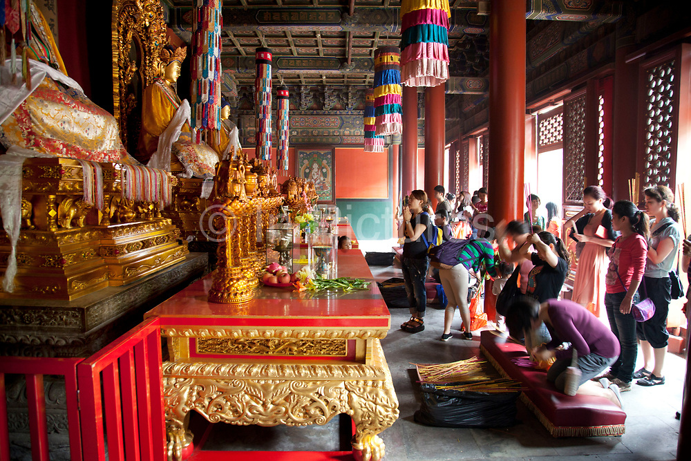 """People praying inside one of the main buildings at Yonghe Temple, also known as the """"Palace of Peace and Harmony Lama Temple"""", the """"Yonghe Lamasery"""", or - popularly - the """"Lama Temple"""" is a temple and monastery of the Geluk School of Tibetan Buddhism located in the northeastern part of Beijing, China. It is one of the largest and most important Tibetan Buddhist monasteries in the world. The building and the artworks of the temple is a combination of Han Chinese and Tibetan styles."""