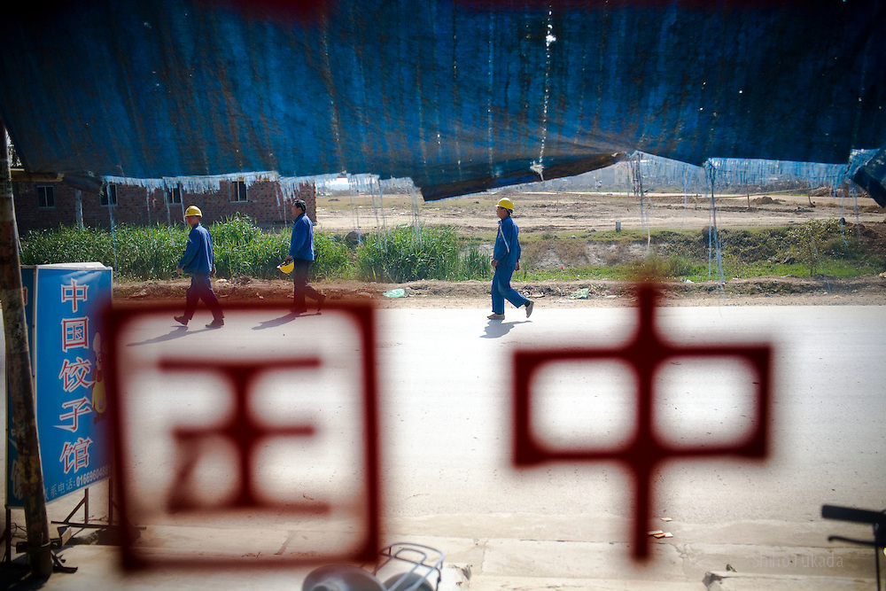 """Workers are seen through a window with """"China"""" in Chinese character near the Haiphong Thermal Power Plant construction site in Trung Son, Vietnam, Nov. 22, 2009. At the construction site here, a few miles northeast of the port city of Haiphong, an entire Chinese world has sprung up, including four walled dormitory compounds for the Chinese workers, restaurants with Chinese signs advertising dumplings and fried rice, and currency exchange shops."""