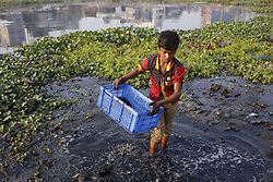 January 2, 2018 - Dhaka, Bangladesh - A boy cleans leftover of burn wire to get copper for sell in dirty water at Buriganga River. (Credit Image: © Md. Mehedi Hasan via ZUMA Wire)