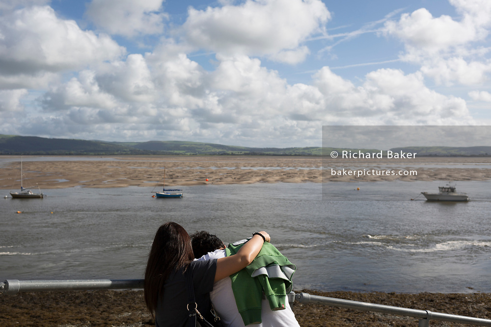 A couple hug while looking out across the estuary at low-tide of the River Dovey, on 12th September 2018, in Aberdovey, Gwynedd, Wales.