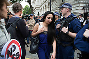 London, UK. Wednesday 27th May 2015. Members of the public pass as police guard Downing Street as students demonstrate in Westminster against Tory Party cuts. The protest was focussed on a number of subjects including spending cuts but generally was a mark of displeasure and concern as to what the Conservatives will do while in power.
