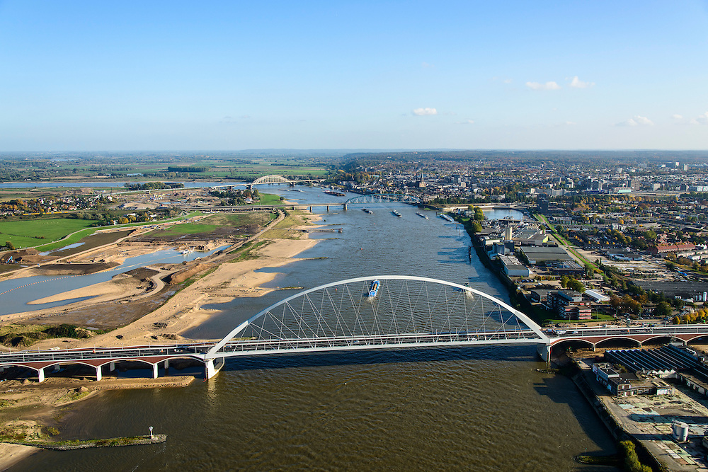 Nederland, Gelderland, Nijmegen, 24-10-2013; de nieuwe stadsbrug van Nijmegen over rivier de Waal, De Oversteek. Daarachter de spoorbrug met fietspad (De Snelbinder) en de laatste brug is de Waalbrug. Links van de rivier grondwerkzaamheden voor de Dijkteruglegging Lent (Ruimte voor de Rivier). Links Nijmegen-Noord, rechts binnenstad.<br /> First bridge the new city bridge of Nijmegen on the river Waal, De Oversteek (The Crossing). Next the railway bridge with cycle path De Snelbinder (The Luggage strap) and finally the Waal bridge. To the left of the river groundwork for the Dike relocation of Lent (project Ruimte voor de Rivier: Room for the River). Nijmegen city on the horizon.luchtfoto (toeslag op standaard tarieven);<br /> aerial photo (additional fee required);<br /> copyright foto/photo Siebe Swart.
