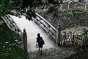 Tokyo, Oji - A young japanese womane cross a traditional wodden bridge.