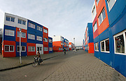 """Living In Containers<br /> By Ton Koene<br /> <br /> The Netherlands is a country with one the highest population density. Especially in the 'randstad', the heart of the Dutch ecomony, consist of Amsterdam, Rotterdam, Utrecht and Den Haag (7 million people) . The Randstad is together with London, Paris, the Flemish Diamond and the German Rhine / Ruhr area one of the main urban concentrations in northwest Europe. <br /> <br /> The area has turned into a busy beehive were land is scars and every square meter needs to be used effectively. Prices of land and housing have gone through the roof. As a result, many families have decided to leave this congested area and move to villages and towns less populated. <br /> <br /> However, many do need to live in this economical heart as they have jobs there or study. Talking about students: serious shortage of cheap housing has made it problematic for students to find accommodation. A company in Holland (Tempo housing) has found a solution: Keetwonen (keet=container, wonen=living). <br /> <br /> In 2007, they built a small city out of containers just outside the centre of Amsterdam; Over 1000 used sea containers have been converted into apartments and stacked as Lego blocks onto each other. It is the biggest container village ever built in the world. Tempo housing has designed, developed and built these temporary housing units especially for students. <br /> <br /> Living in a converted shipping container is a new concept in the Netherlands. It turned out to be a big success under students in Amsterdam and it is now one of the most popular student dormitories in the Netherlands. The student housing foundation """"De Key"""" (www.dekey.nl) in Amsterdam takes care of the administration and supervises the buildings. There is an official waiting time of 2 years but most students can move in much faster. In fact most students who inhabited the containers have been living here from the beginning when the units were built.<br /> <br /> The e"""