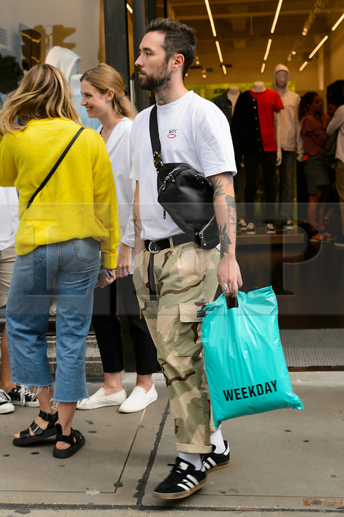 © Licensed to London News Pictures. 18/08/2017. London, UK. Customers leaving with shopping bags at the opening of H&M group's first Weekday clothing store in Regent Street. Weekday is know for its offerings and minimalist styles, with 27 stores throughout Europe. The store is next to the H&M Arket lifestyle store. Photo credit: Ray Tang/LNP