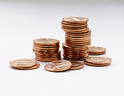 Various stacks and loose pennies on a white table