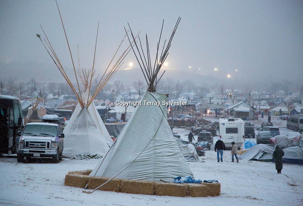 Police floodlights illuminate the route of the Dakota Access oil pipeline on a snowy winter morning in the pipeline opposition camp on Thanksgiving Day, November 24, 2016. Cannon Ball, North Dakota, United States.