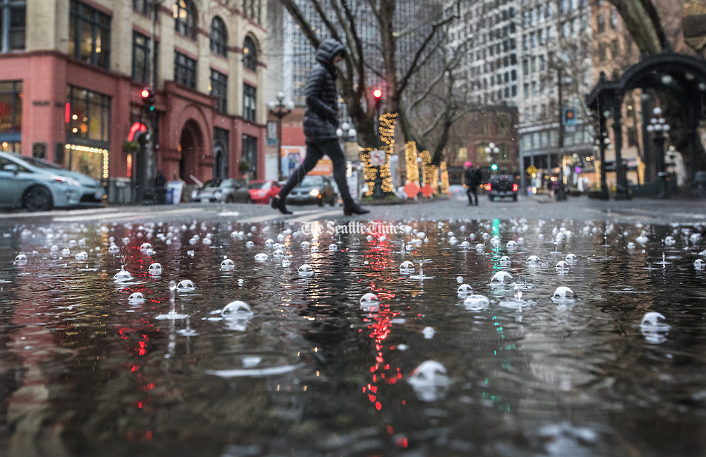 A puddle bubbles up in the rainfall on First Avenue in downtown Seattle. (Steve Ringman / The Seattle Times)