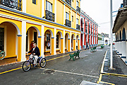 A woman rides her tricycle past the brightly painted colonnaded style Hotel Posada Doña Lala along the Venustiano Carranza pedestrian walkway in Tlacotalpan, Veracruz, Mexico. The tiny town is painted a riot of colors and features well preserved colonial Caribbean architectural style dating from the mid-16th-century.