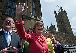 © London News Pictures. 11/05/2015. Leader of the SNP Nicola Sturgeon (centre in red top) is applauded by 56 SNP Members of Parliament outside the St Stephens Entrance to the Houses of Parliament as they arrive at Westminster following their election sucess. Photo credit: Ben Cawthra/LNP