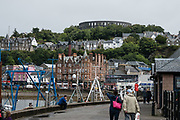 Seen from Oban Ferry Terminal, McCaig's Tower rises prominently on Battery Hill overlooking the town of Oban in Argyll, Scotland, United Kingdom, Europe. It is built of Bonawe granite with a circumference of 200 meters with two-tiers of 94 lancet arches. The structure was commissioned by the wealthy, philanthropic banker (North of Scotland Bank), John Stuart McCaig, his own architect. The tower was built between 1897 and his death in 1902, intended as a lasting monument to McCaig's family and as employment for local stonemasons during winter. As an admirer of Roman and Greek architecture, McCaig had planned for an elaborate structure based on the Colosseum in Rome, but only the outer walls were completed. Oban is an important tourism hub and Caledonian MacBrayne (Calmac) ferry port, protected by the island of Kerrera and Isle of Mull, in the Firth of Lorn.
