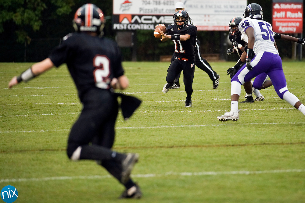 Trojans wide receiver Hunter Foreman (2, left) is open as quarterback Damian Bertino (11, center) rolls out his way during the Cox Mill Chargers at Northwest Cabarrus Trojans high school football game on Friday night.