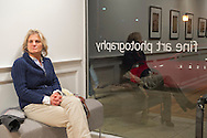 Huntington, New York, U.S. - March 1, 2014 - A visitor sits on a bench near the front window at the Opening Reception '3 Wild & Crazy Artists' at FotoFoto Gallery.