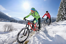 Two young man in sportswear riding mountain bike in snow