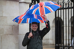 © licensed to London News Pictures. London, UK 09/05/2013. A man trying to shelter himself with two umbrellas under the rain in central London on Thursday, 09 May 2013. Photo credit: Tolga Akmen/LNP