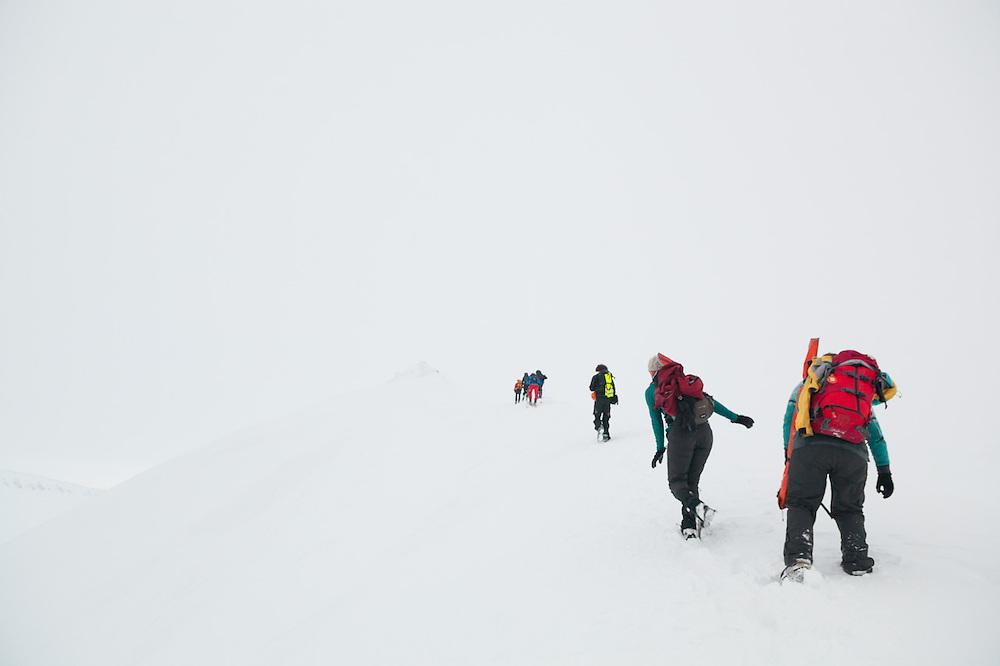 UNIS students from nearby Longyearbyen hike towards the summit of Nordenskioldfjellet, Svalbard.